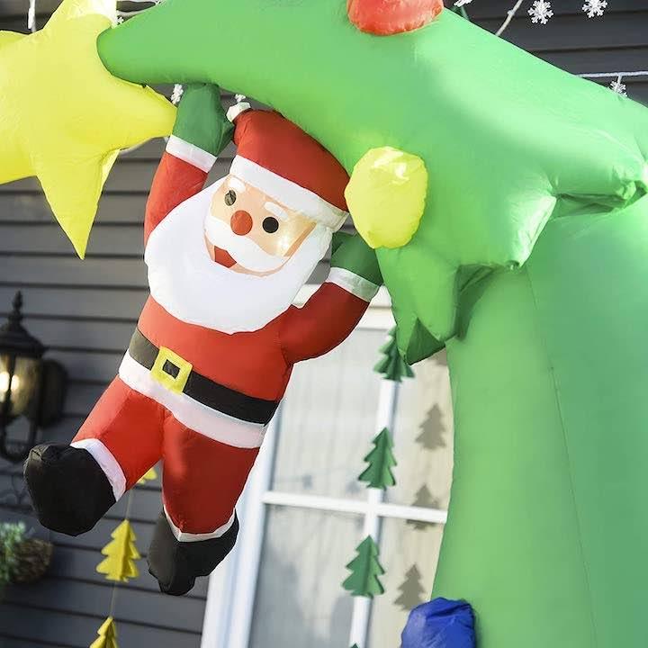 Weihnachtsmann-haengt-an-Baumspitze-aufblasbarer-Weihnachtsbaum